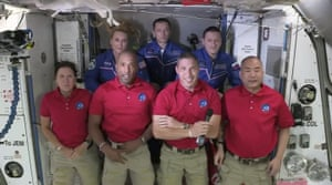 The SpaceX astronauts stand behind the International Space Station crew after docking