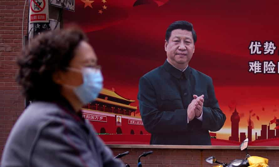 A woman in a facemask walks past a poster of Xi Jinping on the street