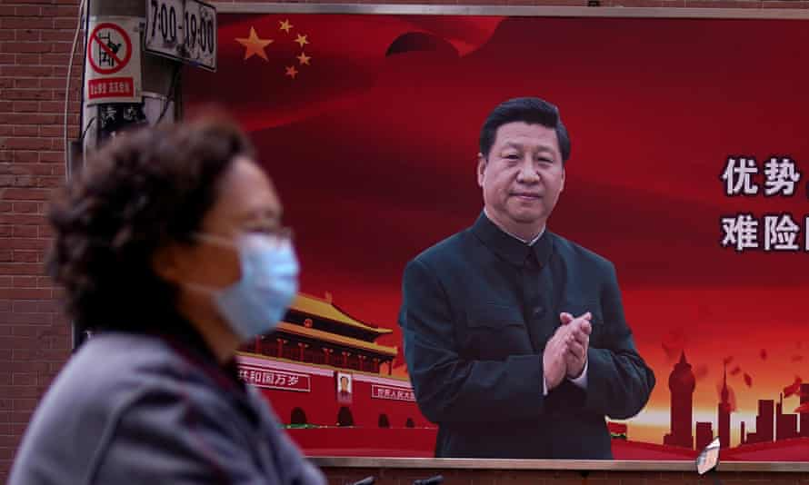 A woman wearing a protective mask passes a portrait of the Chinese president, Xi Jinping.