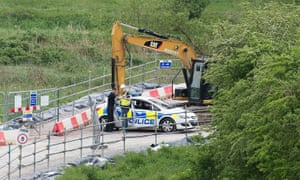 A digger with a police car next to it at a construction site