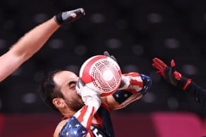 Canada's Zak Madell and Travis Murao attempt to stop Charles Aoki of the United States during their wheelchair rugby pool game, which the Americans won