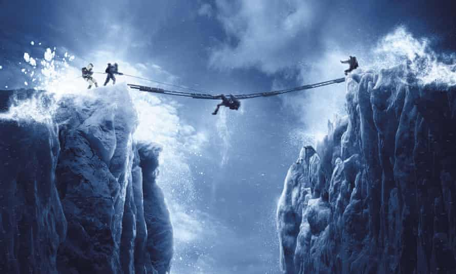 A rope suspended between two mountain peaks with someone crawling along it and others at either end