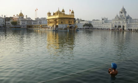 An Indian Sikh devotee takes a dip in the holy sarovar at the Golden Temple.