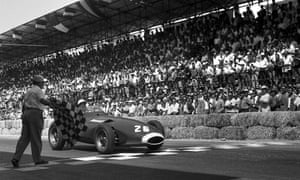Stirling Moss raises his arm as he crosses the finish line to win the Pescara Grand Prix in Italy during August 1957.