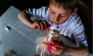 A young boy playing with a Barbie doll