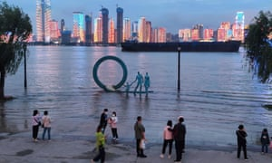People stand next to overflowing section of Yangtze River in Wuhan, where coronavirus was first identified.
