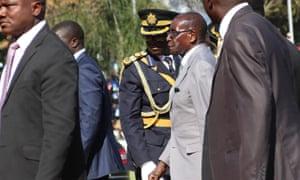 Zimbabwean president Robert Mugabe surrounded by bodyguards.