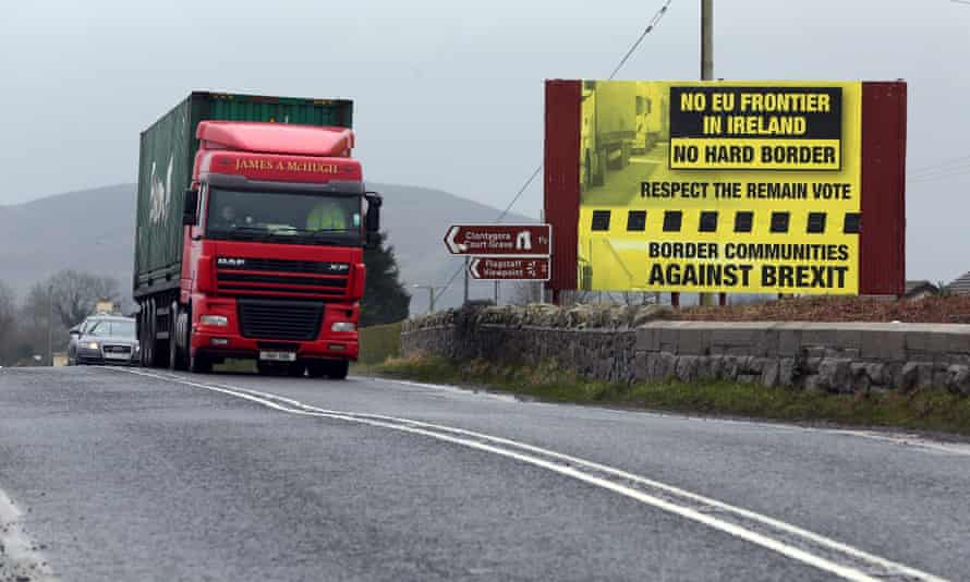 Trafic crosses the border into Northern Ireland from the Irish Republic next to a poster protesting against a hard Brexit near Dundalk.