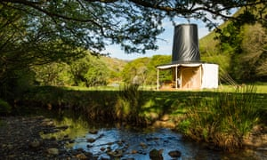 Daytime and in bright sunshine. The Black Hat cabin, designed to look like a traditional Welsh hat is seen in a field by a river.