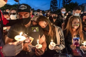 Rafael Farias, left, the father of nine-year-old Matthew, mourns with Rosie Farias, centre, and Mary Alcaraz, right, during a candlelight vigil for the victims of the Orange shooting outside the offices of Unified Homes