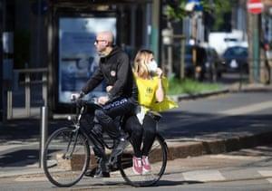 People wearing protective masks ride a bike in Milan