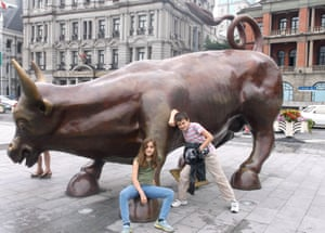 The children posing next to a large statue of a bull
