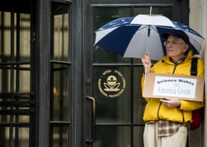 A protester seeks shelter from the rain in front of the EPA during the Science March, in which thousands rallied in Washington.