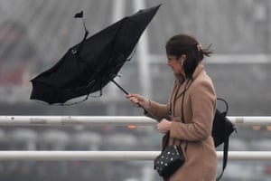 A woman holds an umbrella, blown inside-out by the wind, as she walks across Waterloo Bridge in London