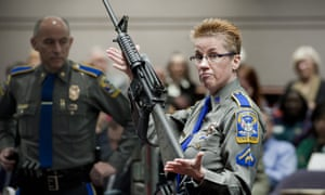 A firearms training unit of the Connecticut state police holds up a Bushmaster AR-15 rifle, the same make and model of gun used by Adam Lanza in the Sandy Hook School shooting.