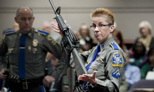Detective Barbara J Mattson, of the Connecticut state police, holds up a Bushmaster AR-15 rifle, the same make and model of gun used by Adam Lanza in the Sandy Hook school shooting.