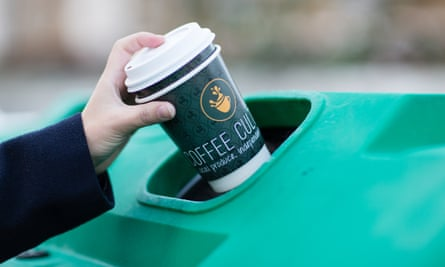 A disposable coffee cup is put into a recycling bin