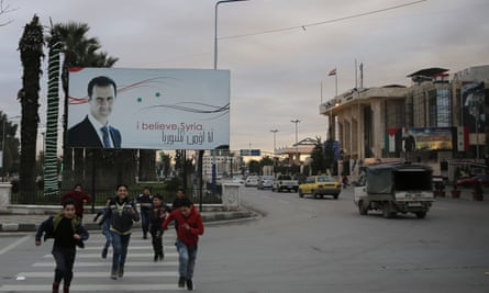In Aleppo, Syrian children cross a street in front of a banner showing the Syrian president, Bashar al-Assad