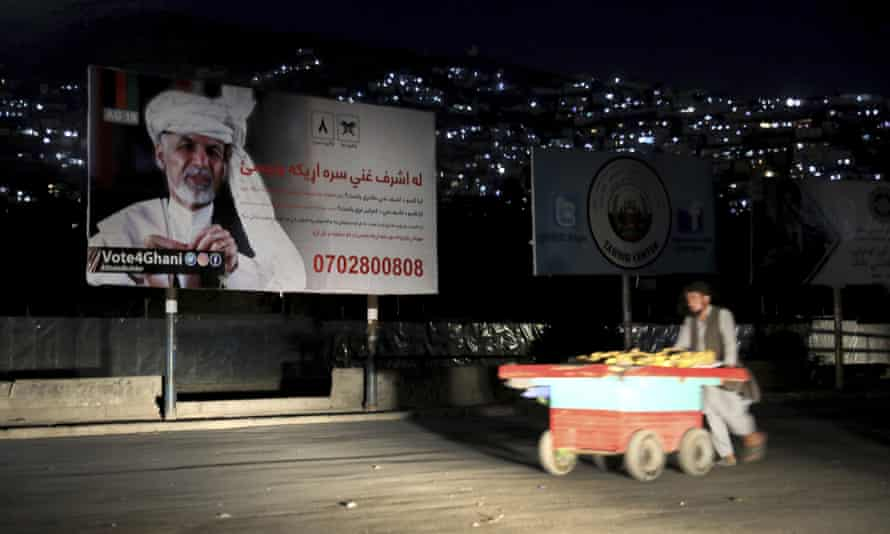 A street vendor in Kabul passes an election poster for the Afghan president, Ashraf Ghani, who is seeking a second term at this month's election.