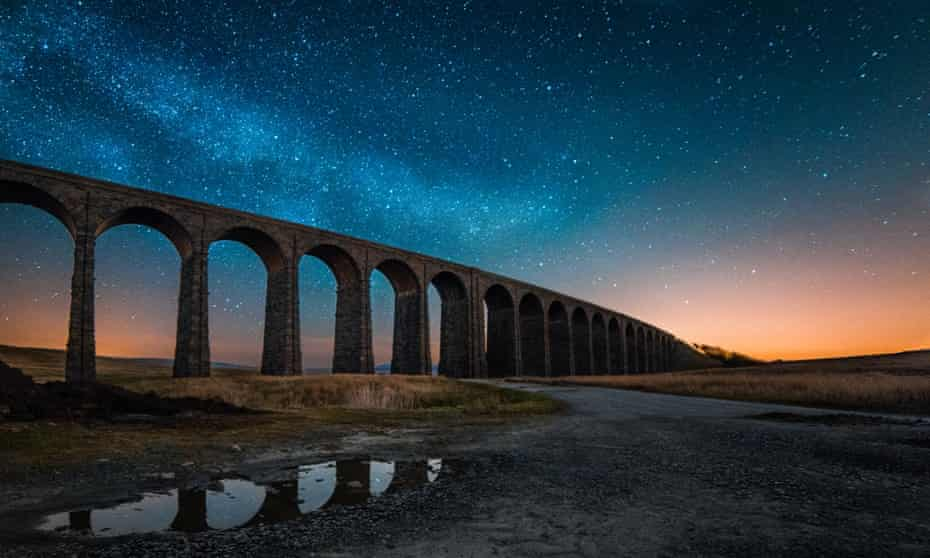 Ribblehead viaduct, Yorkshire Dales national park. Photo shows a starry night and sunset afterglow.