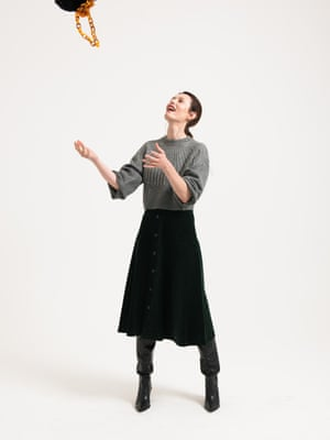 Model wears grey sweater, £49.99, and dark green corduroy skirt with belt, £49.99, both zara.com. black knee length boots, £179.99, mango.com. Bag, £25, topshop.com.