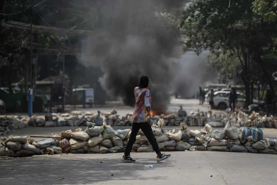 A demonstrator in front of a barricade during protests against the military coup in Yangon on Saturday, 27 March.