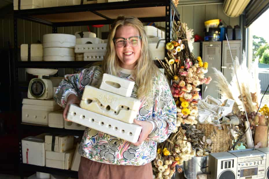 blonde woman in glasses holding pottery moulds