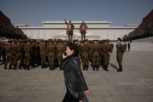 A woman talks on a mobile phone as soldiers from the Korean People's Army look on