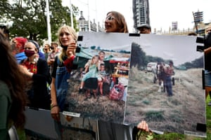 Women hold up pictures of encampments at rally