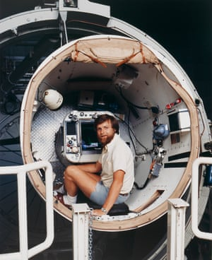 Bearded man in shorts and short-sleeved shirt inside a large tube with lots of wiring and machinery