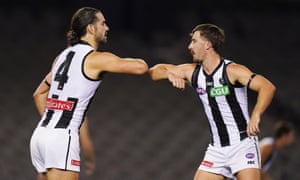 Brodie Grundy of the Magpies celebrates a goal with Tom Phillips