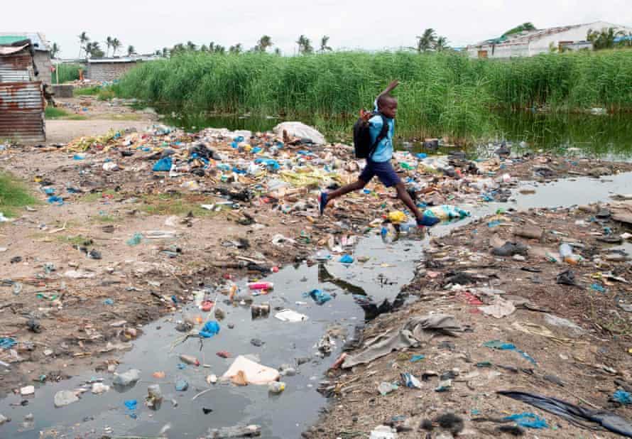 A young boy jumps across a stream in Praia Nova village in Beira, Mozambique