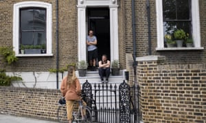 Friends speak from a social distance of 2 meters outside a house in East London on April 25, 2020 in London, England.