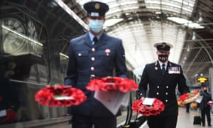 Poppy wreaths are carried into London Paddington to be laid around the station's war memorial