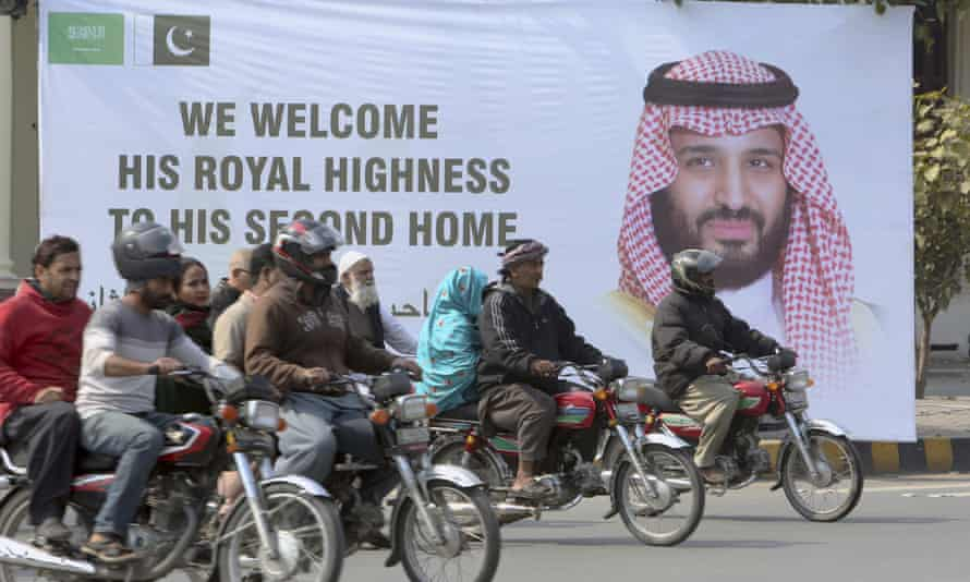 Pakistani motorcyclists pass by a banner welcoming Saudi Arabia's Crown Prince Mohammed bin Salman