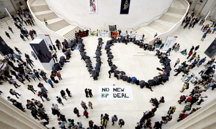 Protesters carrying umbrellas spell out 'no' to a new deal with BP sponsoring cultural institutions