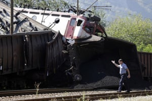 A police officer walks past the site of a train crash in Bosnia
