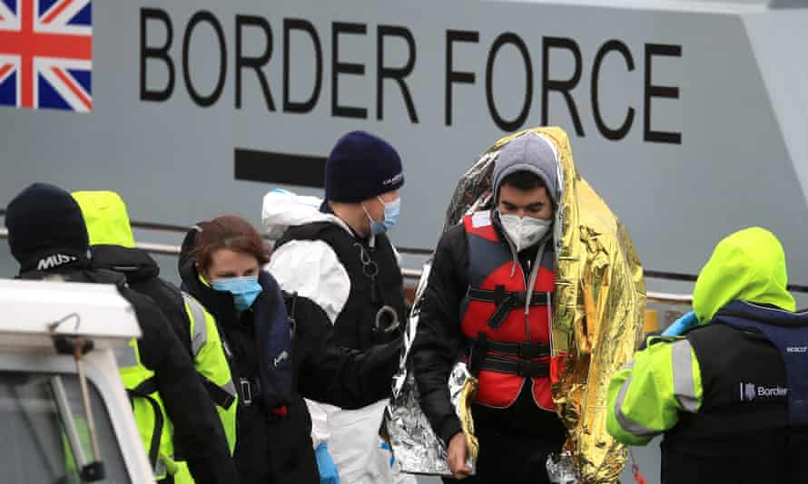 Border Force officers accompany rescued migrants in Dover, Kent