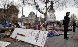 Police officers stand alongside wooden pallets on Place de la République in Paris