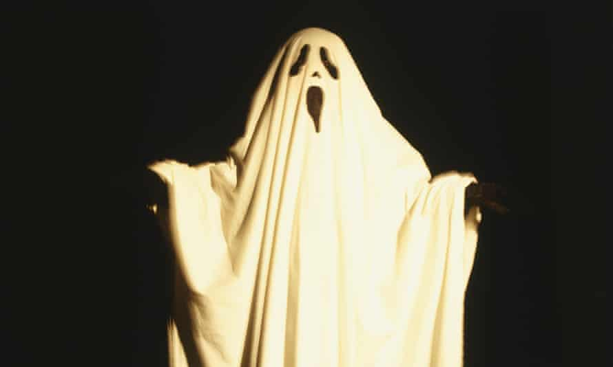 Child dressed up as ghost draped with white sheet that has facial features cut out, extending arms to the sides, front view.