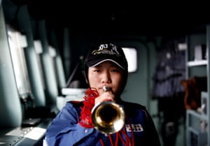 Yuma Osaki, a navigator, prepares to blow a bugle on the bridge of the Kaga as it departs Jakarta port, Indonesia, for naval drills in the Indian Ocean