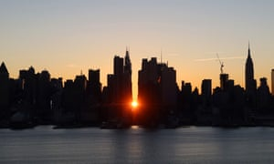 The sun rises above 42nd Street during a Manhattanhenge sunrise or reverse Manhattanhenge as seen from Weehawken, New Jersey