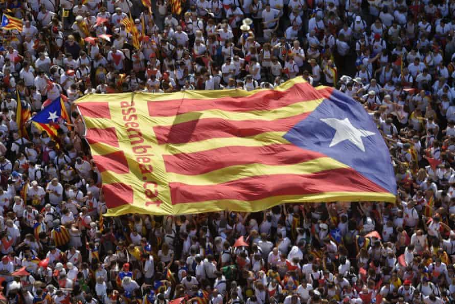 Demonstrators unfold a big Estelada flag during celebrations on Catalan National Day.