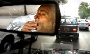 A taxi driver smokes a cigarette while driving his cab in downtown Cairo, Egypt, on 6 July 2014.