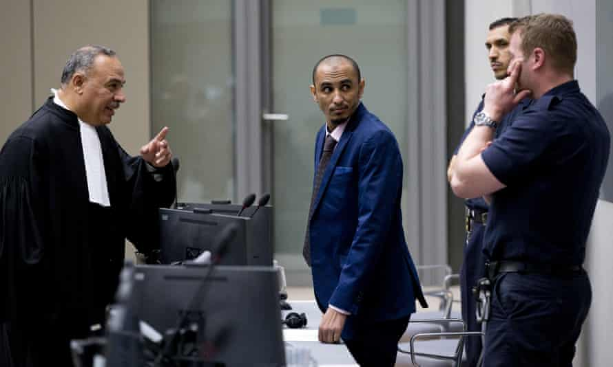 Al Hassan Ag Abdoul Aziz Ag Mohamed Ag Mahmoud (centre) listens as his counsel talks to security guards at the ICC in April 2018.