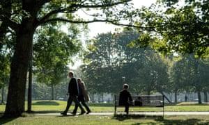 Man sat on bench with two people walking past in Bruntsfield Links Park, Edinburgh.