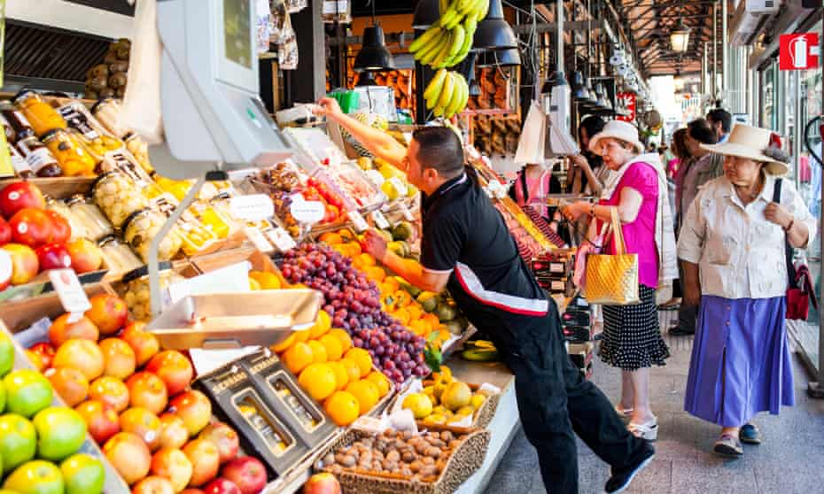 Elderly people shop for fruit and veg at the San Miguel market in Madrid