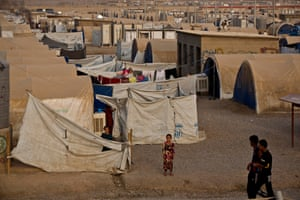 Children play among rows of dust-covered tents in a camp for people displaced from Mosul, in northern Iraq