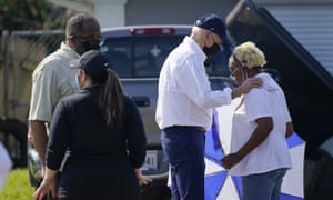 Joe Biden talks with a resident as he tours a neighborhood impacted by Hurricane Ida.