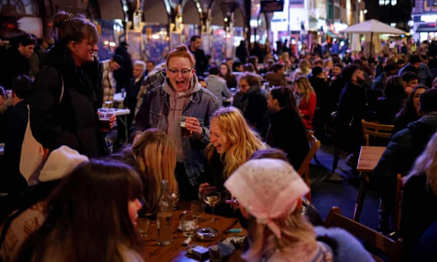 Customers enjoy drinks at tables outside the pubs and bars in Soho, central London